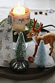 Christmas arrangement of miniature Christmas trees, deer ornament and lit candle in glass inside moss wreath