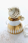 Upturned, vintage teacup with gold pattern and hand-painted Christmas bauble on origami paper star