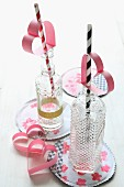 Two drinking straws decorated with pink, paper hearts in retro glass bottles on painted coasters