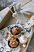 Star-shaped gingerbread biscuits in bowls on hand-painted fabric; hand-sewn soft toy rabbit holding sign