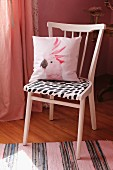 Upcycling: pink-painted kitchen chair with black and white seat cushion and scatter cushion with cockatoo motif