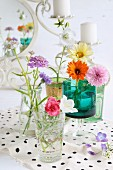 Romantic, still-life arrangement of colourful wildflowers in various glasses on polka-dot fabric