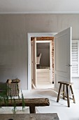 Rustic wooden bench and wooden stool next to door in living room painted pale grey