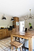 Solid-wood dining table and stool and kitchen counter in rustic kitchen with pale terracotta floor
