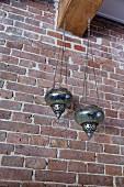Orientalische Windlichter an Holzbalken vor Backsteinwand