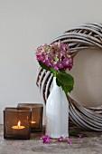 Windlichter aus Rauchglas und Hortensie in weisser Retro Vase vor Kranz aus hell lasierten Weidenzweigen