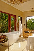 Pleasant bathroom painted beige with free-standing bathtub, wicker armchair and open French windows