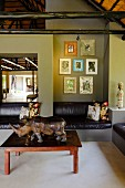 Fitted leather couch along one wall and rhino ornament on coffee table in lounge area with green-painted walls