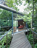 Wooden boardwalk with direct access to interior of concrete house through sliding glass wall