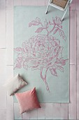 Rug printed with floral motif on pale pink surface