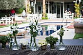 White flowers in crystal vases on wooden table in front of pool and several seating areas