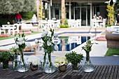 Kristallvasen mit weissen Blumen auf Holztisch, im Hintergrund Pool und mehrere Sitzplätze