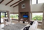 Grosszügiger Wohnraum mit weissen Polstermöbeln um Flokati, Wandnische mit Fernseher zwischen Fenstern mit Sitzpolsterauflagen und eingebauten Schubladen