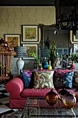 Interior with pink couch, ethnic art and eclectic ambiance
