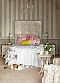 Double bed with geometric patterns on scatter cushions and tall headboard in bedroom with elegant, vintage ambiance