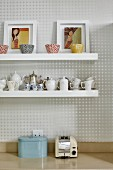 Artistic bowls, framed pictures of women and coffee services on white floating shelves on wall with geometric wallpaper