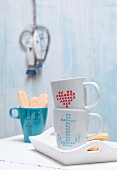 Plain coffee mugs decorated with cross-stitch patterns drawn on with porcelain pen