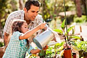 Girl and father watering plants in garden