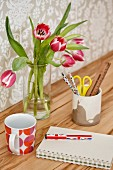 Tulips and mug on desk with pronounced wood grain against wall with pale, patterned wallpaper