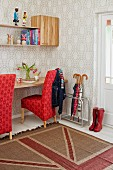 Desk, chairs with red upholstery, wall-mounted shelf and wallpaper with pale pattern