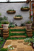 Planted courtyard with steps and wooden planters on wall