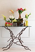 Various vases of king proteas, arum lilies, red tulips, hyacinths, bromeliads and Celosia on glass table with legs shaped like branches