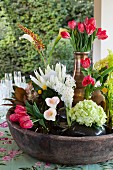 Various vases of king proteas, arum lilies, red tulips, hyacinths, bromeliads and Celosia in large bowl