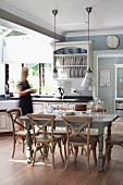 Rustic wooden chairs with backrests made from crossed slats below pendant lamps in spacious, country-house kitchen