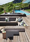 Pool complex on slope with sunken seating area in wooden deck and small, children's pool