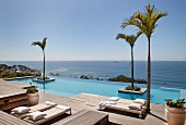Loungers on wooden deck and palm trees in infinity pool with sea view