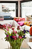 Colourful scatter cushions on couch against large windows of houseboat with view of water
