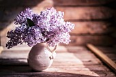 Bouquet of lilac against wooden background