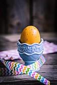 Gelb gefärbtes Ei in Keramik-Eierbecher mit Geschenkband