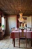 Chandelier, old wooden chairs and striped cloth on table in cosy dining room
