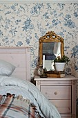Vintage ornaments on bedside table against wallpaper with vintage-style floral pattern