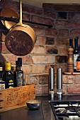 Copper pan, modern spice mills and vintage wooden crate next to gas hob on kitchen worksurface with brick back wall