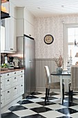 Dining set on chequered floor in rustic kitchen