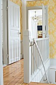 Rustic stairwell with white-painted wooden staircase and ornate yellow wallpaper
