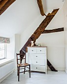 Black-painted wooden chair and white chest of drawers in front of exposed wooden roof beams in attic room