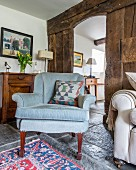 Pale blue, antique armchair in front of rustic wooden board wall with view into hallways through open doorway