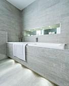 Eingebaute Badewanne mit grauen Fliesen an Frontseite und an Wand, oberhalb schmale, beleuchtete Nische mit Spiegel an Rückwand