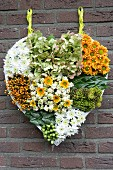 Hand-made, heart-shaped arrangement of chrysanthemums, hydrangeas and berries hung on brick wall
