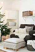 Fur blanket and cushions on comfortable armchair, footstools, corner cabinet and branches of Christmas tree