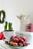 Dish of red apples and fir branches next to hyacinths in white pot
