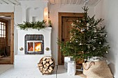Decorated Christmas tree next to fire in old fireplace and basket of firewood on floor in rustic interior