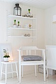 White-painted armchair and romantic arrangement on stool below String shelves on white wooden wall in rustic interior