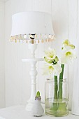 Table lamp with white lampshade and turned base next to glass jar of white amaryllis