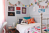 Bunting above metal bed with colourful scatter cushions
