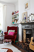 Red velvet armchair next to antique open fireplace decorated with fairy lights