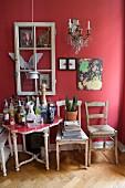 Zimmerecke mit Hausbar auf antikem Tisch vor roter Wand mit Fensterrahmen als Dekoelement